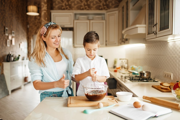 Mother with son mixing melted chocolate in a bowl