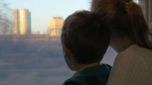 電車で旅行し、日没時に街を離れるときに窓の外を眺める膝の上に息子を持つ母親