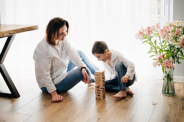 물리적 기술 타워의 게임을하는 아들과 어머니