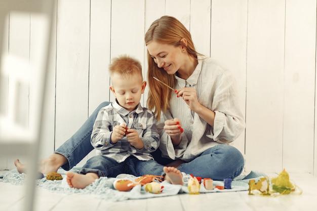 自宅でイースターを準備する息子を持つ母
