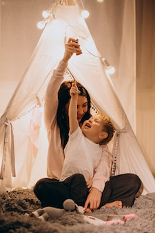 Mother with son sitting in cozy tent with lights at home on christmas