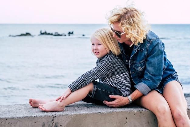 海に対してコンクリートの堤防に座っている息子と母。屋外で子供を気遣う愛情深い母親。休暇中に小さな男の子と余暇を過ごすサングラスの若い女性。