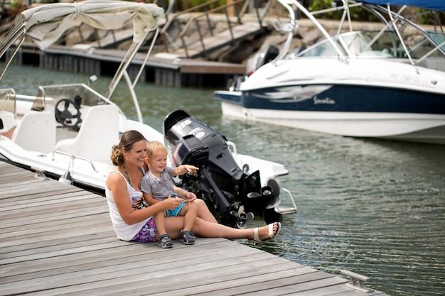 Мать с сыном, сидя на морской пирс. счастливая мать и сын гуляют, смотрят на лодки.
