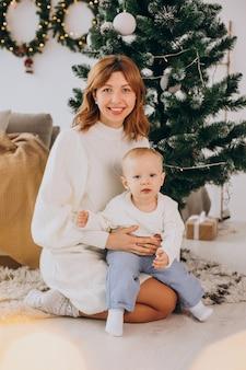クリスマスツリーの下に座っている息子と母