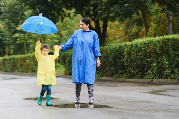 Мать с сыном гуляют под дождем под зонтиком