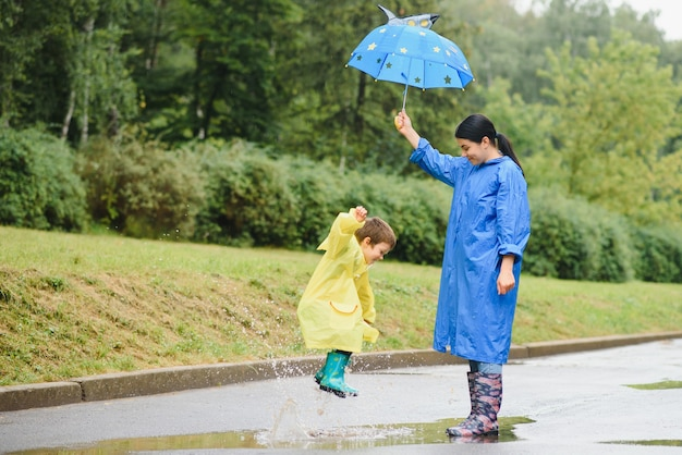 Mother with son walking in the rain under the umbrella