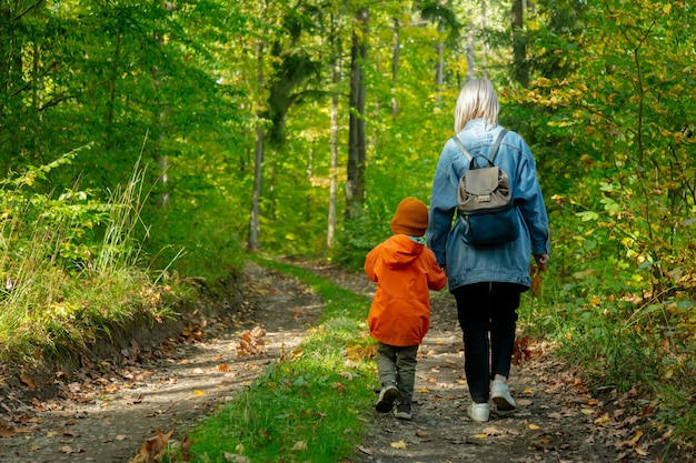 Mother with a son walking on a road in a forest