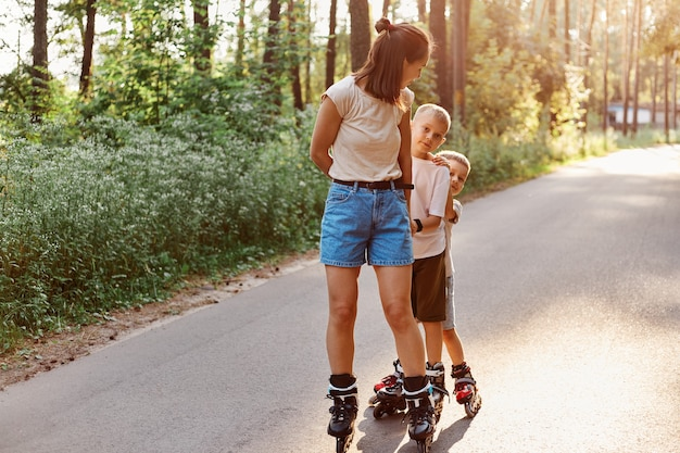 Mother with sons spending time together in summer park, family rollerblading, active pastime, children with mother roller skating outdoor on asphalt road.