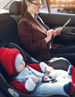 Mother with tablet in her hands and her little son in a baby car seat ride in the back seat of a taxi