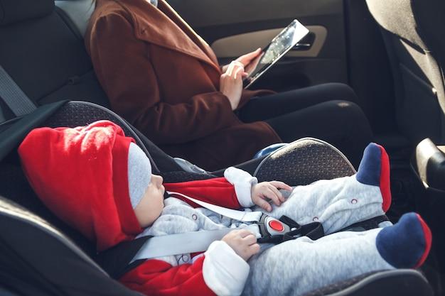 그녀의 손에 태블릿과 아기 카시트에있는 그녀의 작은 아들이 택시 뒷좌석에있는 어머니
