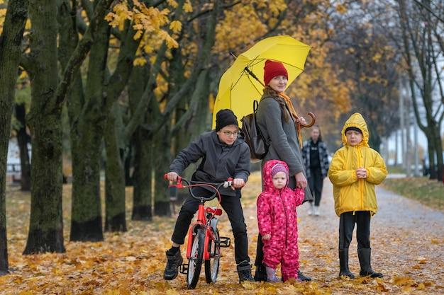 Мать с тремя детьми стоят в парке в осеннем парке. аллея с опавшими листьями.