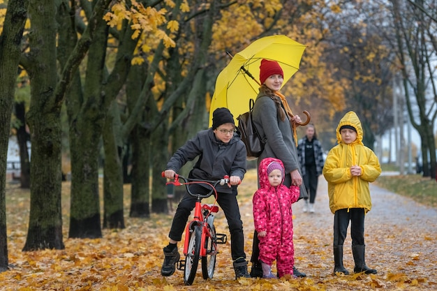 Mother with three children stand in the park in autumn park. alley with fallen leaves.