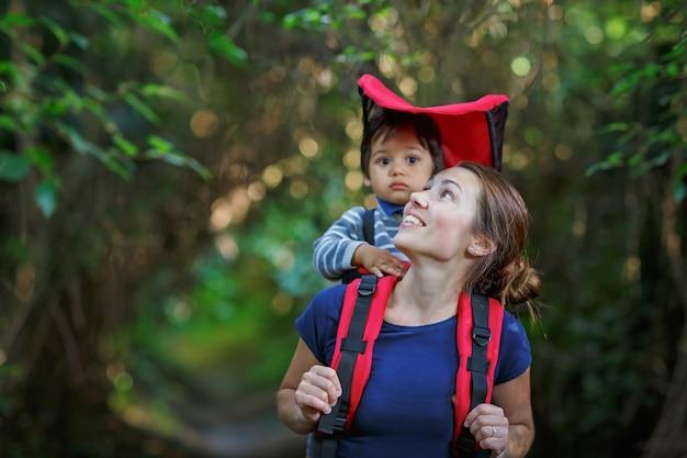 배낭 캐리어에 유아 자녀와 어머니는 숲에서 하이킹