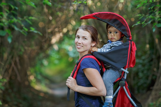 Мать с маленьким ребенком в рюкзаке гуляет в лесу