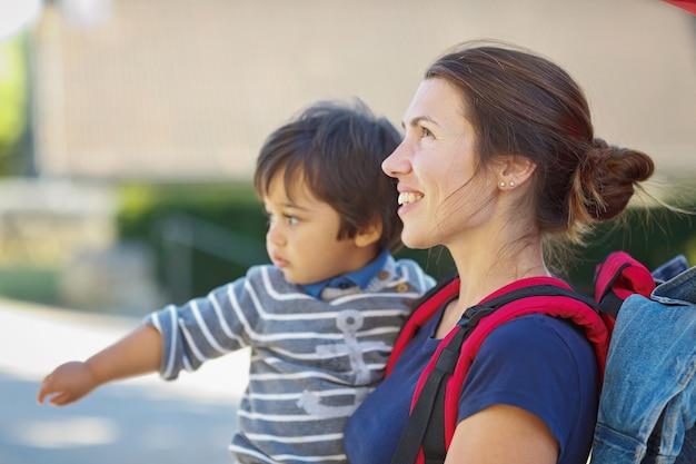 Мать с маленьким ребенком в походе. турист в городе несет на руках ребенка