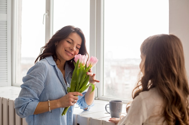 Mother with tulips and daughter standing at window