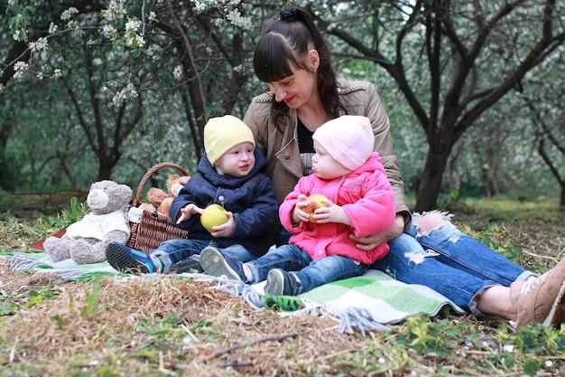Мать с близнецами в весеннем яблоневом цветнике солнечный день