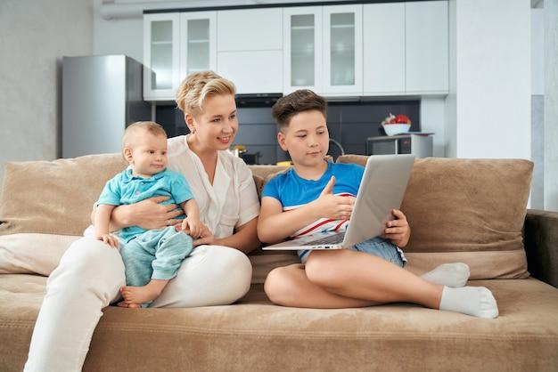 소파에 노트북을 사용하는 두 소년과 어머니