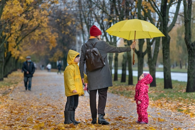 Mother with two children is walking in the autumn park. mom holds a yellow umbrella over her daughter.