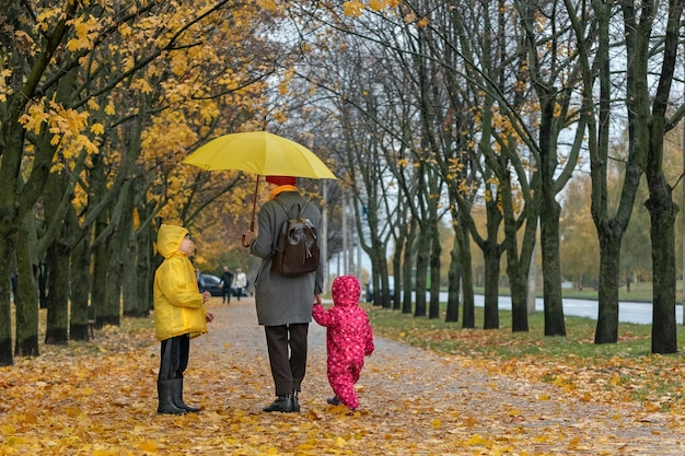 Mother with two children is walking in park with yellow umbrella in the rain. autumn park, fallen leaves. happy family.