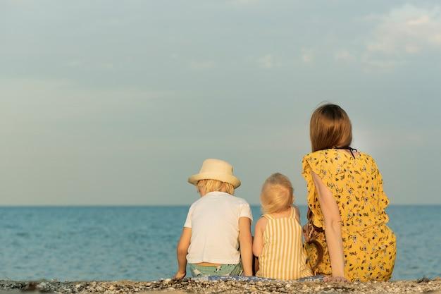 Мать с двумя детьми, сидя на пляже и глядя на море. вид сзади. летний отдых с детьми.