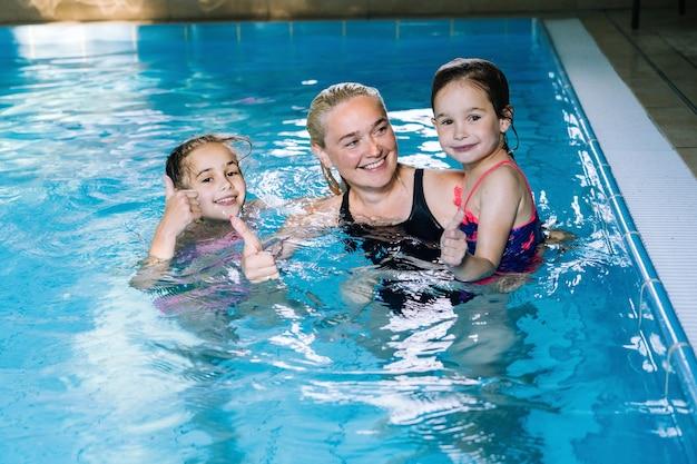 屋内プールで楽しんでいる2人の娘を持つ母