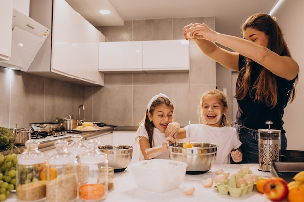 Mother with two daughters at kitchen baking
