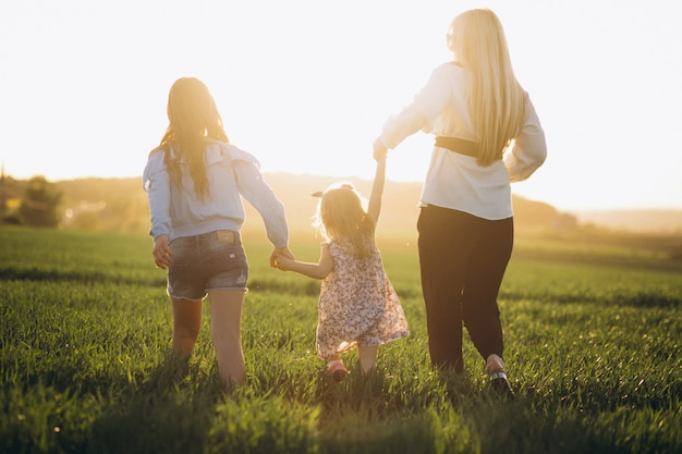 Mother with two daughters in sunset