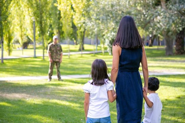 屋外で軍の父に会う2人の子供を持つ母。背面図。家族の再会の概念