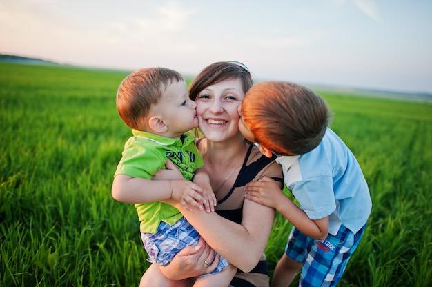 緑の野原に2人の息子を持つ母。