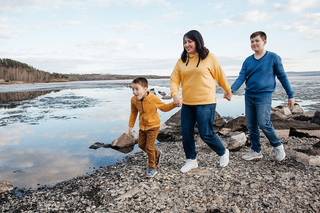 A mother with two sons on the riverbank. mom and her sons are running. outdoor recreation.