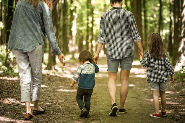 Мать с маленькими дочерьми гуляют в лесу