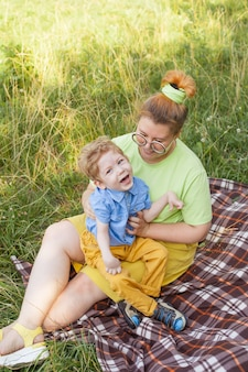 A mother with a young disabled son is resting in a city park on a sunny day. infantile cerebral palsy. disability. rehabilitation of a disabled child. socialization of a disabled person.