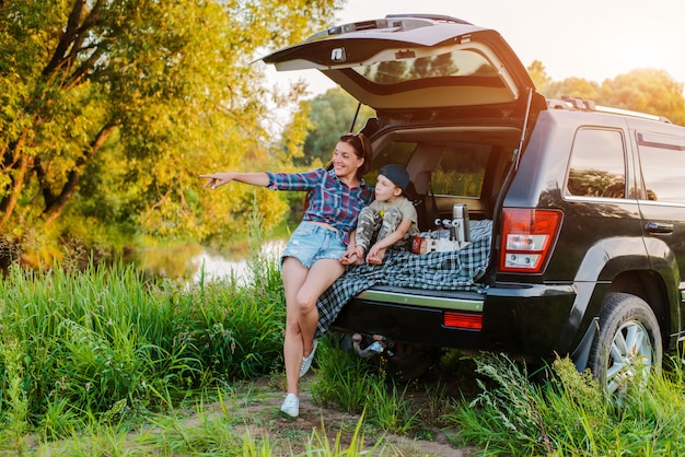 Mother woman and child son comfortably relax in nature by the river sitting on the trunk of a jeep.