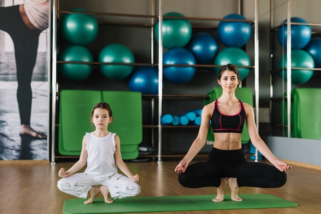 Mother and woman doing yoga together at gym