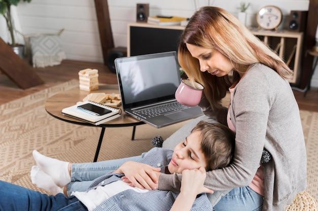 Мать работает из дома и обнимает сына