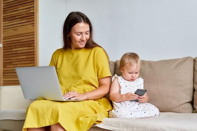 Мать работает дома на ноутбуке, пока дочь серфинг в сети на смартфоне
