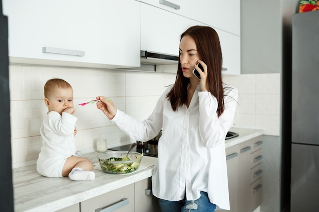 Mother working from home, talking on phone and feed cute small baby