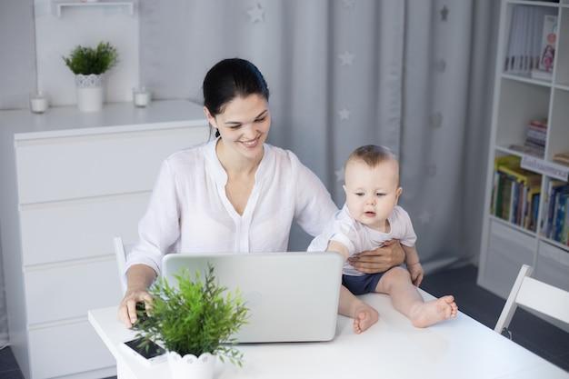 彼女の赤ん坊の息子の隣で働く母 Premium写真