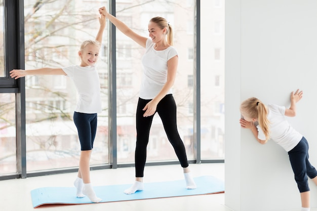 Mother working out with daughters at home on yoga mat