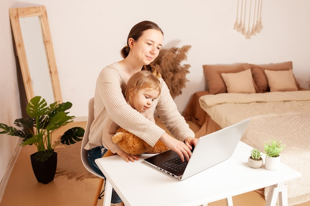 Mother works at home for a laptop the child prevents the work a young woman is freelance with her