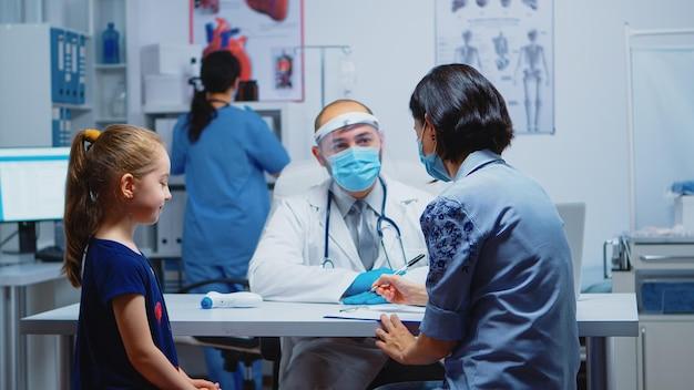 診療所に座っているクリップボードに子供の治療を書いている母親。 covid-19の間に医療サービス、相談、病院での治療を提供するマスクを備えた医学の小児科医の専門家