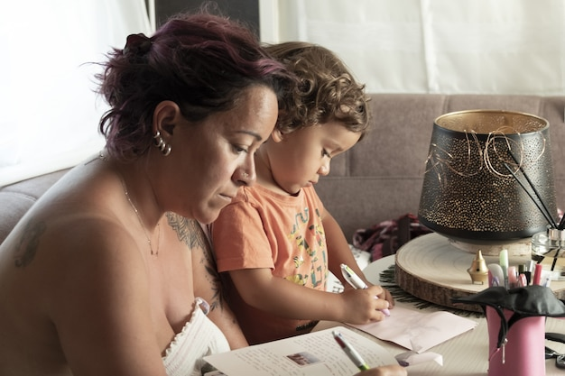 Mother and yearold caucasian son make crafts in caravan while on vacation