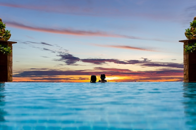 Mother and young son relax in swimming pool watching sunset over ocean on summer vacation.