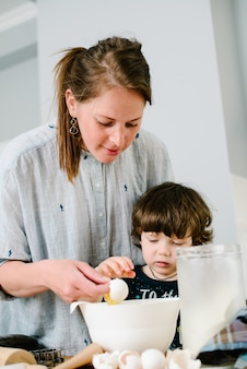 Mother young woman teaching showing her son child how breaking egg into a bowl