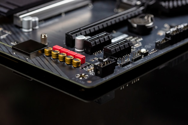 Motherboard on a table close-up, inside of a desktop computer showing chips, circuit boards and components