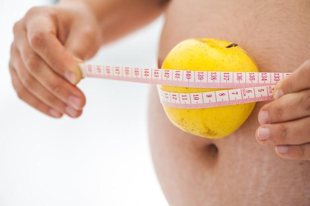 Mothercare. крупным планом беременная женщина, измерения ее живот с лентой, чтобы следить за ростом ребенка