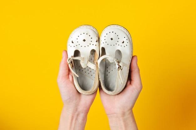 母性、子供の頃のコンセプト。黄色の女性の手のひらに子供の革のサンダル。