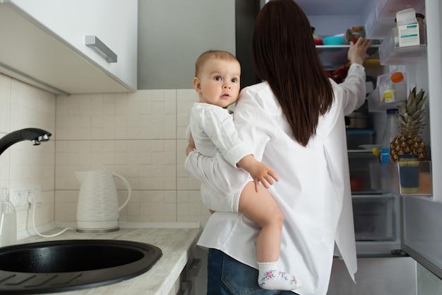 Concetto di maternità e bambini. madre che tiene bambino e che prende cibo dal frigorifero