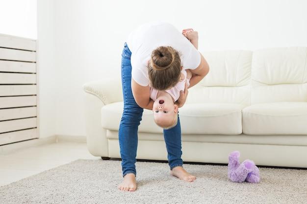 母性、家族、子供たちのコンセプト-家でかわいい赤ちゃんを持つ若い母親。